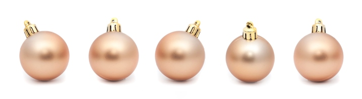 Line of five Gold Christmas balls on a white background with copyspace